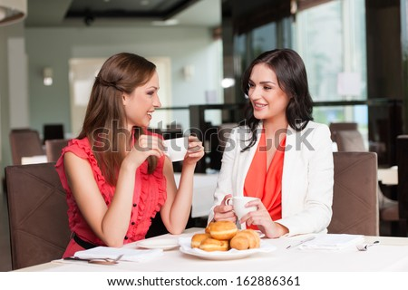 Two girlfriends meet at caf���© for breakfast. Talking and gossiping  - stock photo