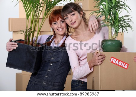 two girlfriends moving in their new apartment - stock photo