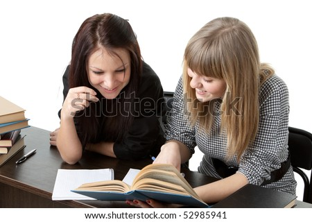 Two girlfriends of the student prepare for examination, sitting at a desk on a white background. - stock photo