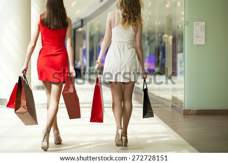 Two girlfriends on shopping walk on shopping mall with bags - stock photo