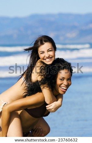 Two girlfriends playing at the beach - stock photo