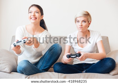 Two girlfriends playing video games  - stock photo