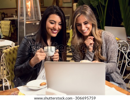 Two girlfriends sharing information while having a coffee - stock photo