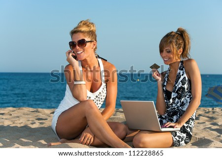 Two girlfriends shopping outdoors with credit card and laptop.
