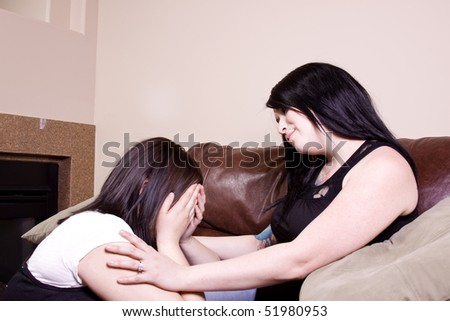 Two Girlfriends Sitting on the Couch - One consoling the other crying girl