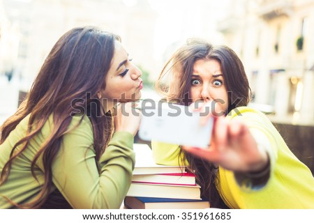 Two girlfriends taking a selfie in a bar outdoors - Students grimacing while looking at camera - Two young beautiful women having fun - stock photo