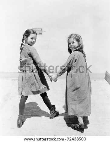 Two girlfriends walking and holding hands - stock photo