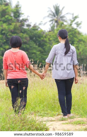 Two girlfriends walking hand in hand