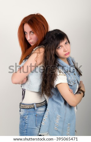 two girlfriends were offended, turned their backs to each other. different emotions. looking away after conflict at home - stock photo
