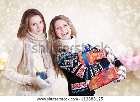 Two girlfriends with christmas presents: disappointed - one and happy smiling - other - stock photo