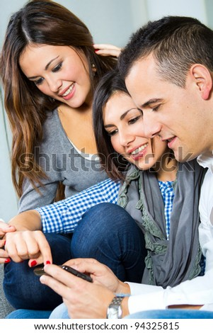 two girls and a boy having fun with a mobile phone on the couch at home - stock photo