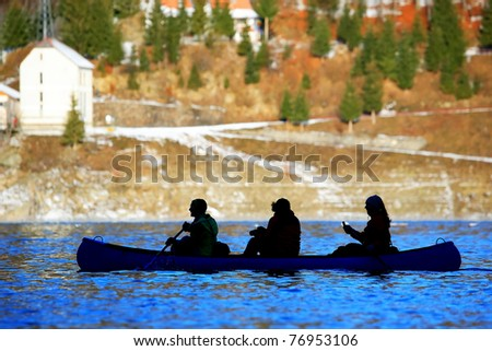 Two girls and a boy paddleing in a canoe - stock photo