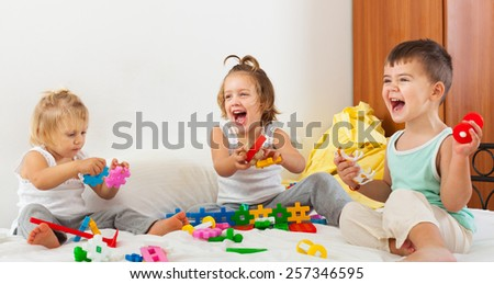 Two  girls and a boy playing on  big bed.  - stock photo