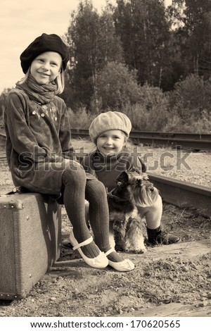 Two girls and a dog go by rail - stock photo