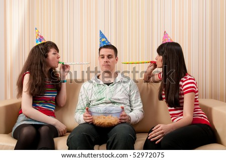 Two girls and a guy in party hats having a birthday party - stock photo