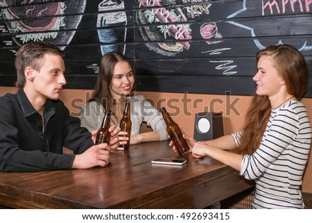 Two girls and a guy sitting in the pub holding in hands bottle of beer
