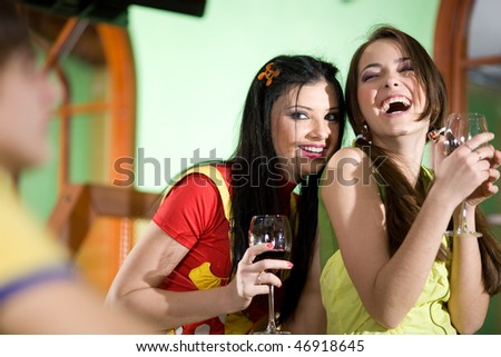 Two girls and boy are drinking wine together - stock photo
