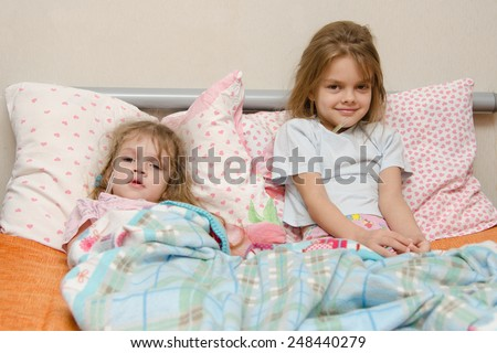 Two girls and four to six years lying in bed meryat temperature thermometer - stock photo