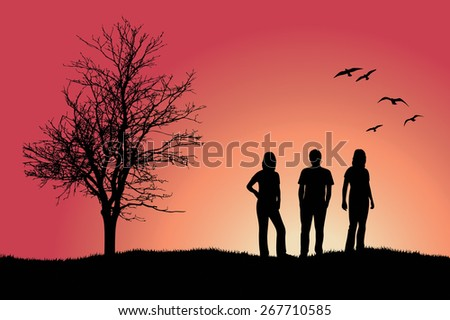 two girls and man standing on hill near bare tree - stock photo