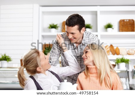 Two girls and the guy have fun in cafe - stock photo
