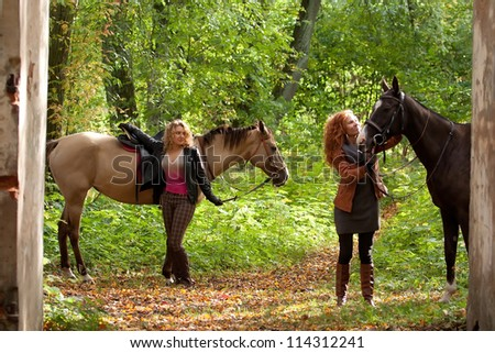 Two girls and two beautiful Akhal-Teke horses in an old park