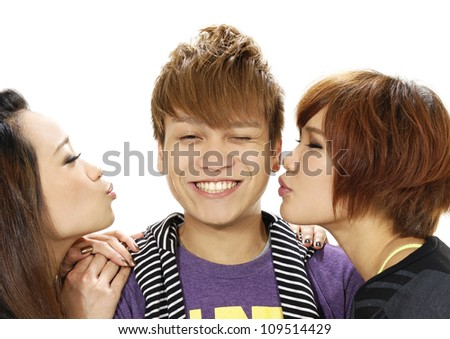 Two girls and young man kisses. Isolated. - stock photo