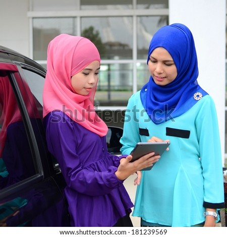 Two girls are busy talking at the car park - stock photo