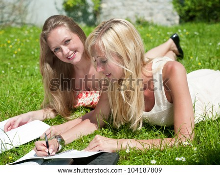 two girls are learning outside in the park - stock photo