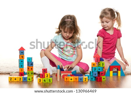 Two girls are playing on the floor