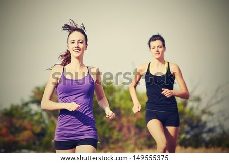 Two girls are running in nature - selective focus - stock photo