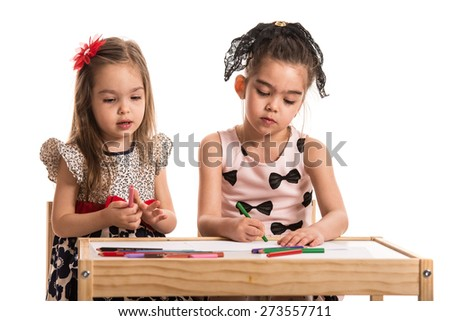 Two girls at kindergarten drawing with colored sketch pens on papers - stock photo