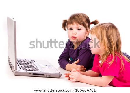 Two girls at the copmuter playing over white background