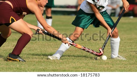 Two girls battle for control of the ball in a field hockey game - stock photo