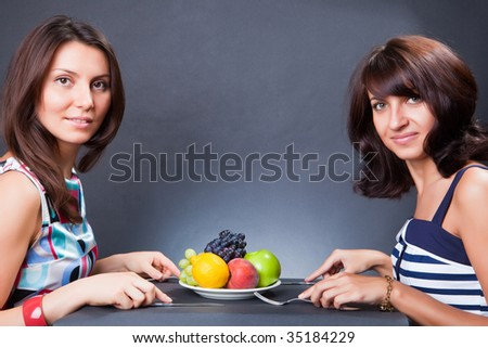 Two girls behind a table and a plate with fruit