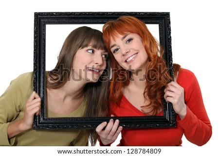 Two girls behind black frame - stock photo