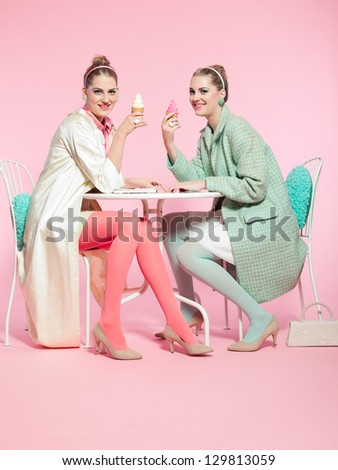 Two girls blonde hair fifties fashion style eating ice cream. - stock photo