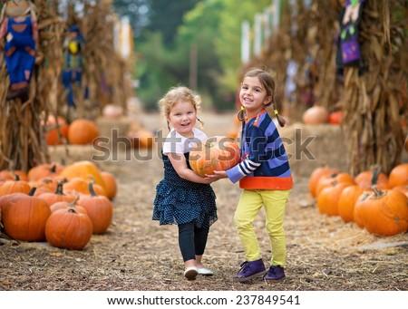 Two Girls Carrying a Pumpkin
