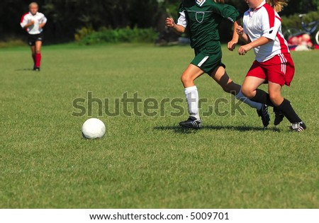 Two girls chase a soccer ball across a grass field. - stock photo
