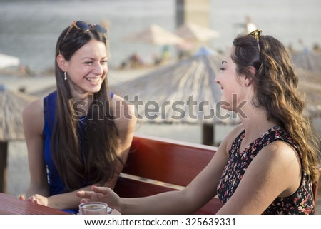 Two girls chatting on beach. Candid shots.