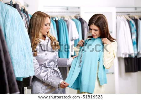 Two girls consider a jacket in shop - stock photo