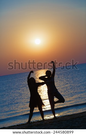 Two girls dancing at sunset on a background of the sea. Focus on models. Shallow depth of field. Toned image. - stock photo