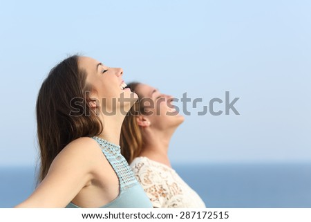 Two girls doing breath exercises inhaling fresh air on the beach  - stock photo