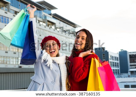 Two girls doing shopping outside - stock photo