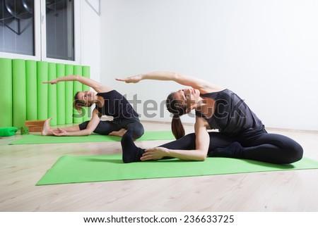 two girls doing yoga - stock photo