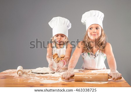 Two girls dressed as chefs making pizza. Children help their parents in the kitchen, roll the dough out of flour rolling pin