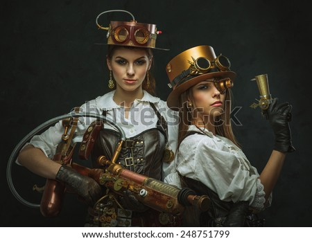 Two girls dressed in the style of steampunk with arms. - stock photo