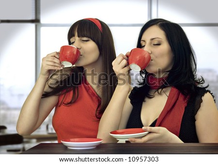 two girls drinking coffee in a cafeteria - stock photo
