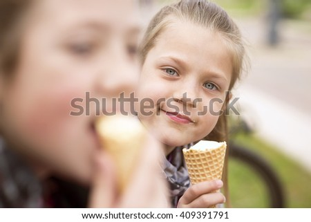 two girls enjoy ice-cream eating outdoor by summer