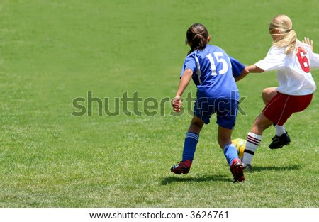 Two girls fighting to get the ball in a soccer game - stock photo
