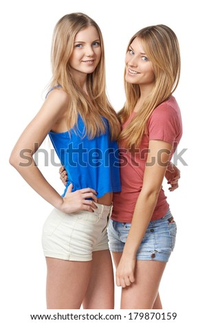 Two girls friends standing against white background - stock photo